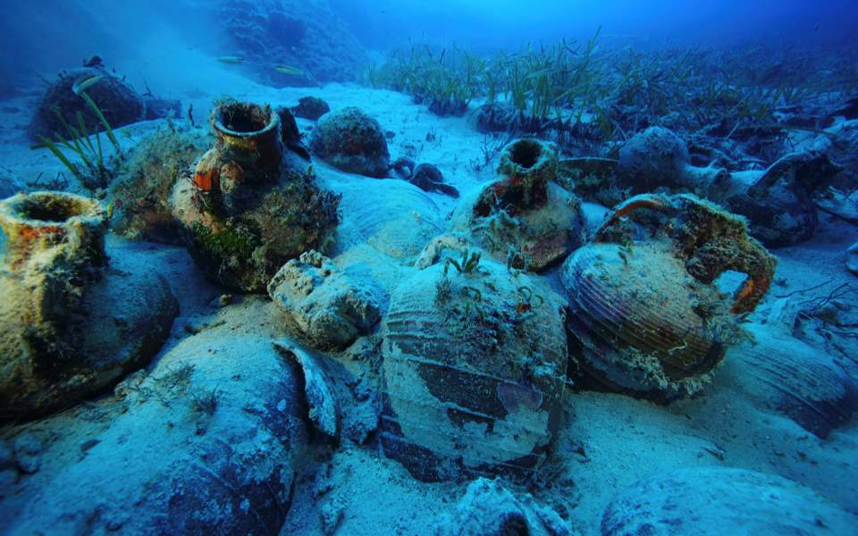 Amphorae are seen at the sea bottom at a shipwreck site